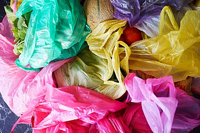 Overhead view of colourful plastic shopping bags of fruit and vegetables - p429m1084565 by Kathleen Finlay