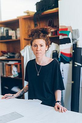 Portrait of fashion designer in her work studio - p429m2058384 by Eugenio Marongiu