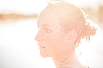 Porträt einer jungen Frau im Gegenlicht - p552m2194521 von Leander Hopf