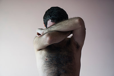 Young man hiding face with arms  - p794m1092329 by Mohamad Itani