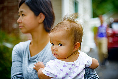 Mid adult woman carrying baby daughter in arms - p924m1557708 by Sue Barr