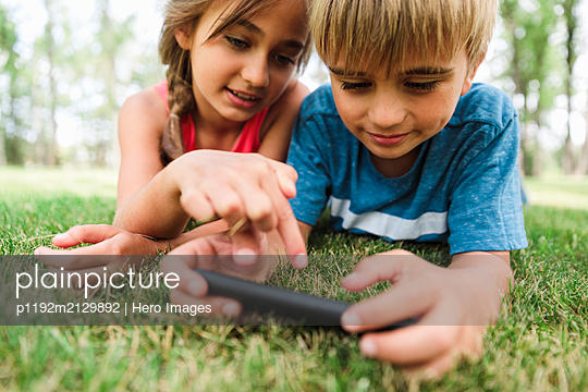 Boy and girl lying on grass using smartphone - p1192m2129892 by Hero Images