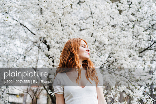 Young woman with eyes closed standing in front of white almond tree - p300m2274555 by Eva Blanco