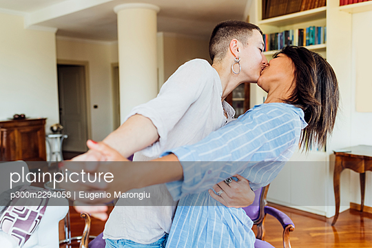 Young gay couple kissing while dancing at home - p300m2294058 by Eugenio Marongiu