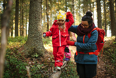 Mother with daughter walking through forest - p312m2191113 by Matilda Holmqvist