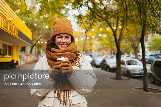 Happy woman holding disposable coffee cup on sidewalk during autumn - p300m2243255 by alev