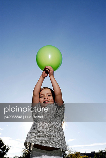 5 years old girl holding a balloon - p4293884f by Luc Beziat