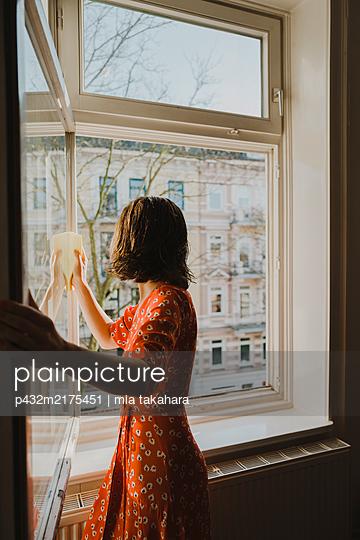 Frau putzt Fenster - p432m2175451 von mia takahara
