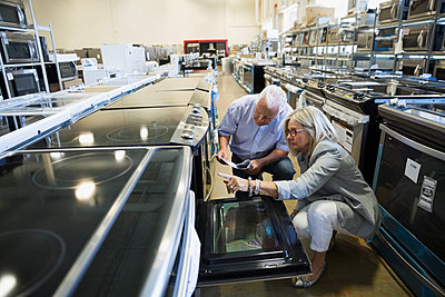 Senior couple shopping for oven in appliance store - p1192m1158312 by Hero Images