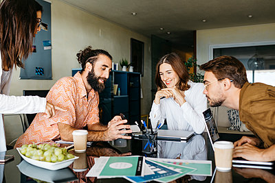 Friends working together on table at home sharing smartphone - p300m2144123 by Josep Rovirosa
