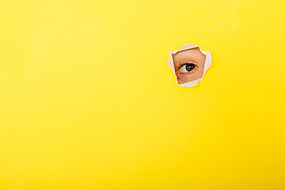 Close-up of boy peeking through torn yellow paper - p300m2198518 by Josep Rovirosa