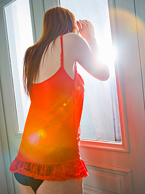Woman looking out o the window - p4130467 by Tuomas Marttila