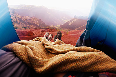 Legs of couple in camping tent in rocky landscape - p555m1231757 by Colin Anderson