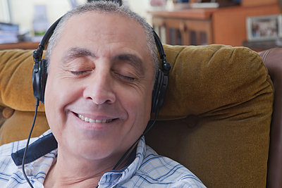 Smiling Hispanic man listening to headphones - p555m1301699 by REB Images