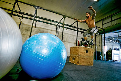 Caucasian man jumping on wooden crate in gymnasium - p555m1304130 by Peathegee Inc