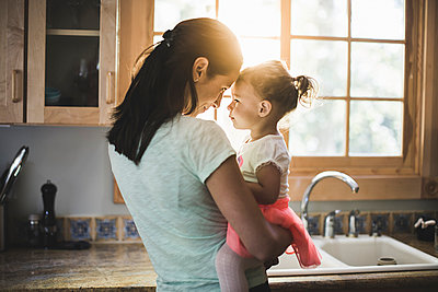 Mother and daughter playing in kitchen - p924m975725f by Chad Springer