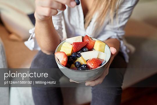 Junge Frau hält eine Schale mit Obst - p1124m1589192 von Willing-Holtz