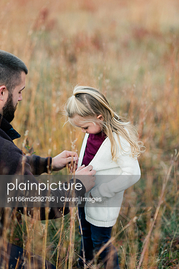 A father helping his daughter put on a cardigan in fall - p1166m2292795 by Cavan Images