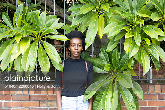African woman between green leaves, portrait - p1640m2260040 by Holly & John