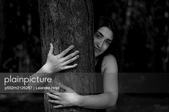 Young woman hiding behind tree trunk - p552m2126287 by Leander Hopf