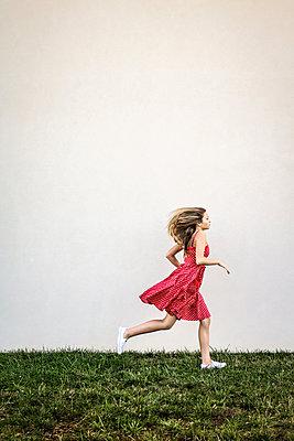 Weiblicher Teenager läuft über eine Wiese - p1019m1496308 von Stephen Carroll