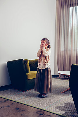 Grl covering her face with her hands while standing in living room - p300m1115168f by Chris Adams