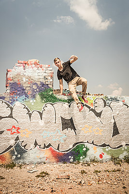 Teenage boy jumping off wall in an old run down industrial area - p300m2206557 by Studio 27