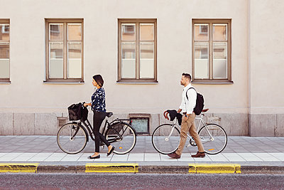 Side view of business colleagues walking with bicycles on sidewalk - p426m1196694 by Maskot