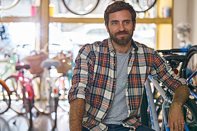 Owner sitting in bicycle shop - p623m2214729 by Frederic Cirou