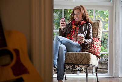 Woman using cell phone in armchair - p924m768454f by C. Camarena