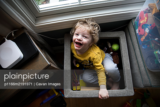 Laughing Boy Sits in Toy Box Next to Storage Bins Looks Up at Camera - p1166m2191971 by Cavan Images