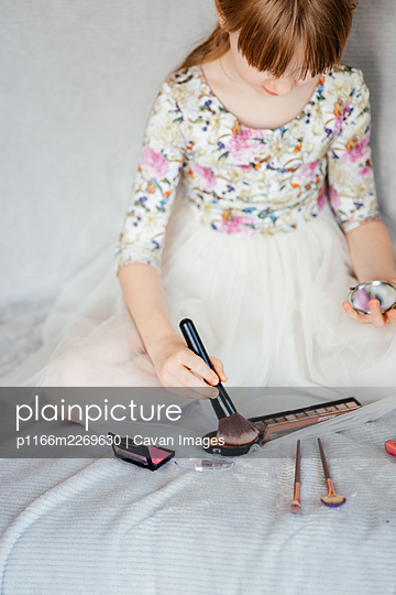 girl secretly does makeup at home - p1166m2269630 by Cavan Images
