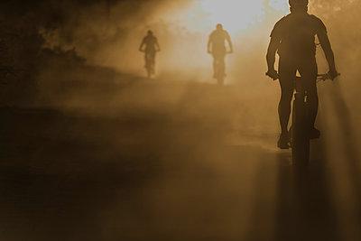 People mountain biking downhill in dust backlit silhouette - p1166m2094396 by Cavan Images