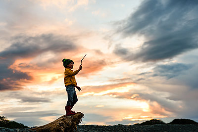 Silhouette of young child holding a stick in the air at sunset - p1166m2165972 by Cavan Images