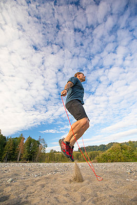 Fit man skips near the Chilliwack River, British Columbia, Canada. - p1166m2202155 by Christopher Kimmel / Alpine Edge Photography