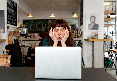 Frustrated young woman using laptop in a cafe - p300m2103264 by FL photography