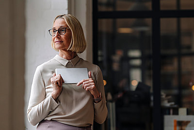 Mature businesswoman holding tablet at the window in office - p300m2155229 by Gustafsson