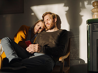 Relaxed couple sitting on bench in sunlight at home with man using cell phone - p300m2166619 by Kniel Synnatzschke