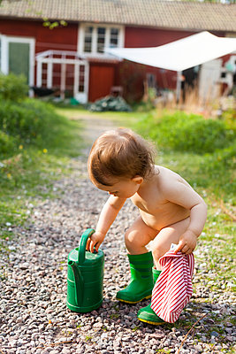 Toddler girl playing in garden - p312m2079402 by Anne Dillner