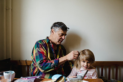 Grandfather helping granddaughter with her hair - p312m2162305 by Stina Gränfors