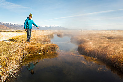 BORAX LAKE, HARNEY COUNTY, OR, USA. A young woman in a blue coat points at steaming hot spring with a look of surprise on her face. - p343m1167978 by David Hanson