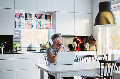 Man with laptop in kitchen - p352m1536604 by Calle Artmark