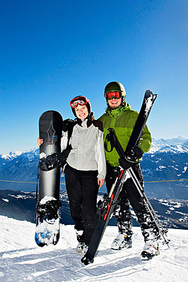 Young couple standing with downhill skis and snowboardan Alps - p3741841 by Juho Heikkinen
