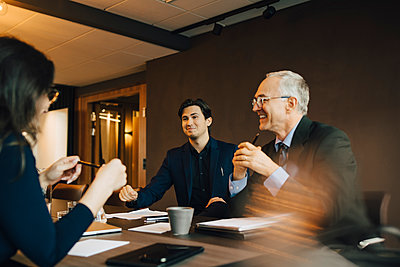 Smiling businessman discussing with male and female colleague in board room - p426m2270652 by Maskot