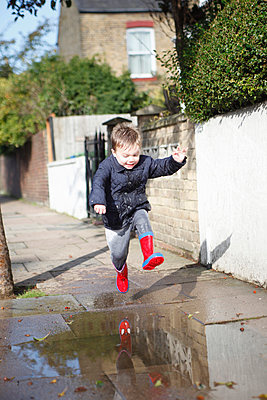 Male toddler in red rubber boots jumping into sidewalk puddle - p429m983450f by Jacabel