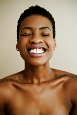 Portrait of smiling Black woman with eyes closed - p555m1301722 by Peathegee Inc