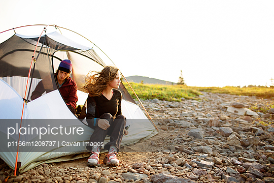 Happy couple relaxing in tent against clear sky - p1166m1209737 by Cavan Images