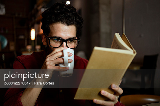 Male professional drinking coffee while reading book in illuminated cafe - p300m2276347 by Rafa Cortés