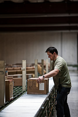 Caucasian warehouse worker in a large distribution warehouse, showing products stored in cardboard boxes, and moving on a motorized conveyor system. - p1100m1575470 by Mint Images