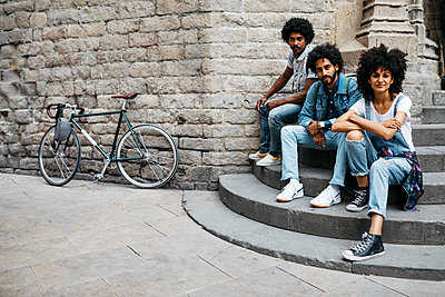 Group of three friends sitting together on stairs in the city - p300m2023919 von Josep Rovirosa